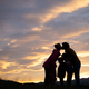 Silhouette of family standing under evening sky with parents giving each other a kiss - PhotoDune Item for Sale