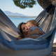 Young mother kissing her toddler daughter hanging in a hammock on the beach - PhotoDune Item for Sale