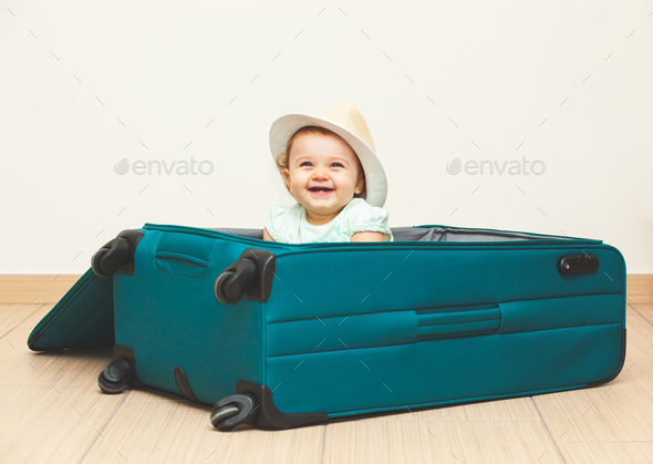 Baby girl sitting in suitcase on the floor with empty background. - Stock Photo - Images