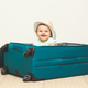 Baby girl sitting in suitcase on the floor with empty background. - PhotoDune Item for Sale