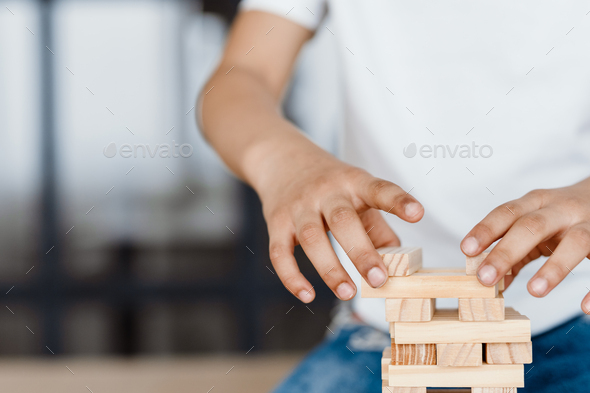 Cropped photo of boy playing with wooden planks at home - Stock Photo - Images