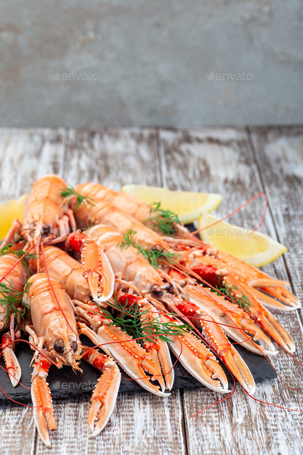Sea crayfishes on stone plate served with dill and lemon, vertical, copy space - Stock Photo - Images