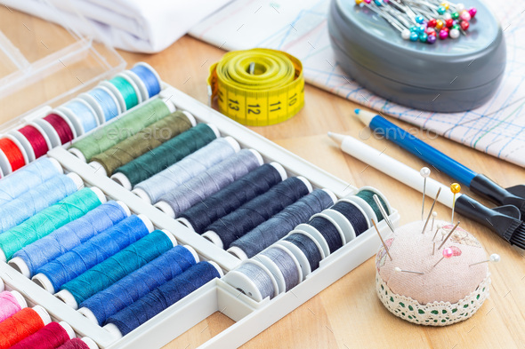 Various sewing accessories, spools and thread, schemes and cloth on wooden table, horizontal - Stock Photo - Images