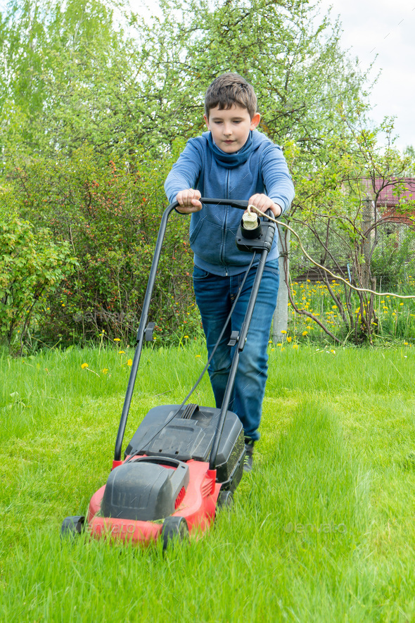 Nine years boy mow grass in backyard or in garden, vertical - Stock Photo - Images