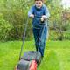 Nine years boy mow grass in backyard or in garden, vertical - PhotoDune Item for Sale