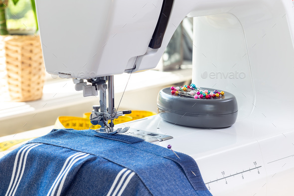 Sewing machine with striped blue white fabric and thread, home crafting or hobby, horizontal - Stock Photo - Images