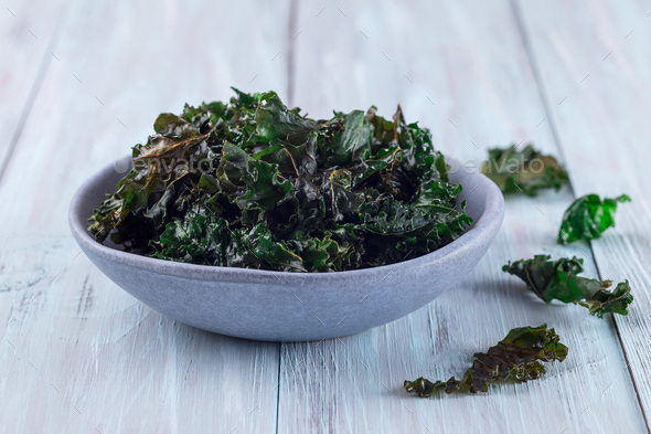 Easy three ingredient baked green kale chips with sea salt and olive oil, in gray bowl, horizontal - Stock Photo - Images