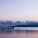 Anonymous persons sitting on pier near sea at sunset - PhotoDune Item for Sale