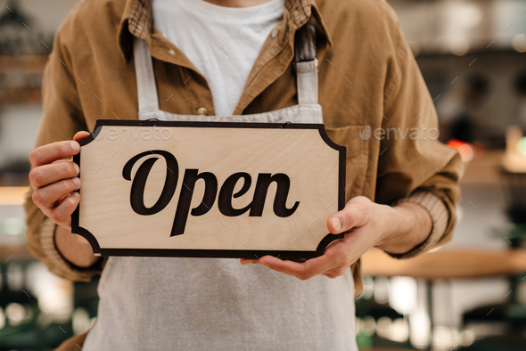 Young man waiter in apron showing open sign - Stock Photo - Images