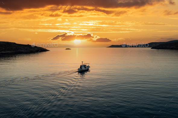 Fishing boat at sunset. Greece. Aerial drone view of typical fishing boat moving on calm sea - Stock Photo - Images