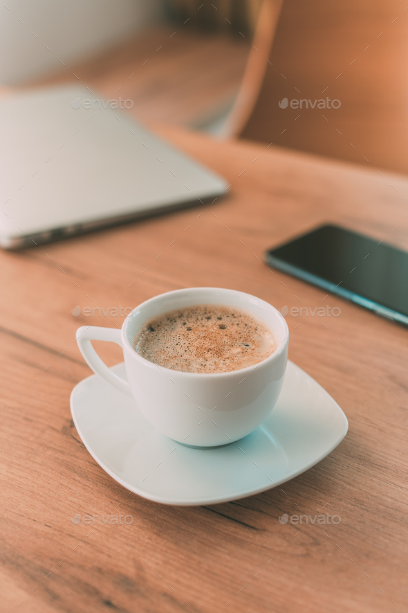Coffee cup with laptop computer and mobile smart phone on freelancer's desk - Stock Photo - Images