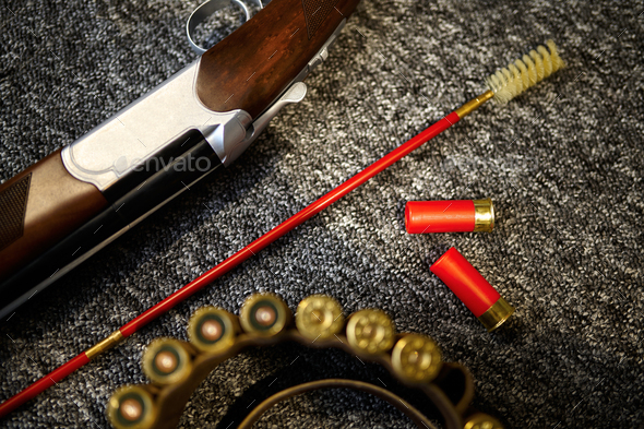 Hunting rifle, bandolier and ramrod in gun store - Stock Photo - Images