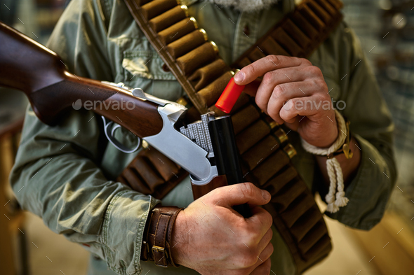 Male hunter with bandolier loads rifle, gun store - Stock Photo - Images