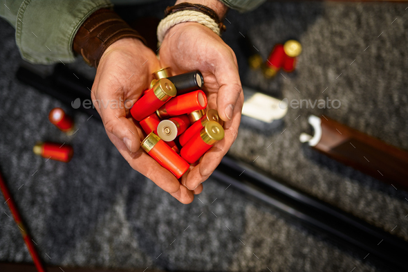 Male hunter hands holds cartridges in gun store - Stock Photo - Images
