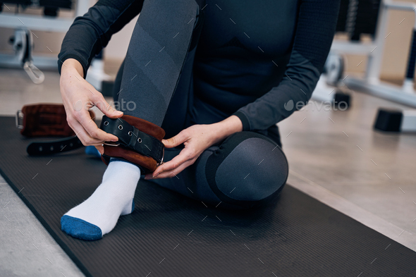 Pretty caucasian woman in black sportwear wearing cuffs of ankle support. Protection and anti-sprain - Stock Photo - Images