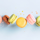 Vintage pastel colored French macaroons or macarons in motion falling on light blue background - PhotoDune Item for Sale