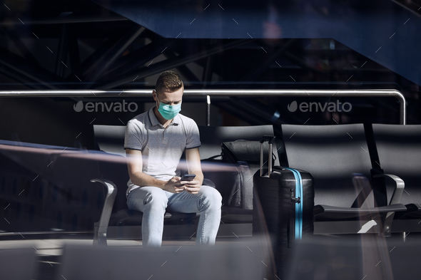 Man waiting in airport terminal and using phone - Stock Photo - Images