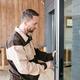 Young repairman fixing lock in large transparent door - PhotoDune Item for Sale