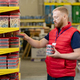 Bearded sales manager putting containers with nails on shelves - PhotoDune Item for Sale