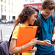 two university students walking in city looking at mobile phone - PhotoDune Item for Sale