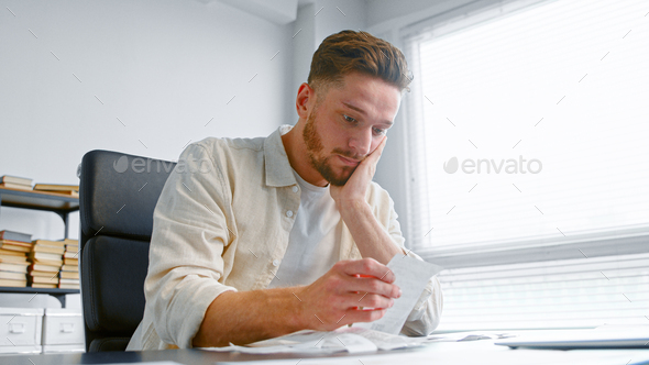 Shocked man bank accountant with beard looks at paper checks and puts hand on head - Stock Photo - Images