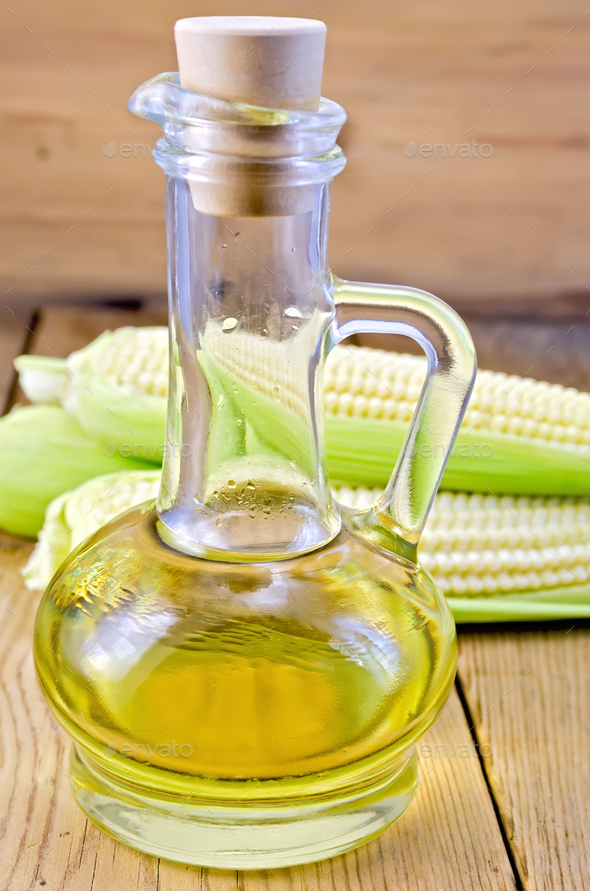Corn oil in a carafe with corn cobs on board - Stock Photo - Images