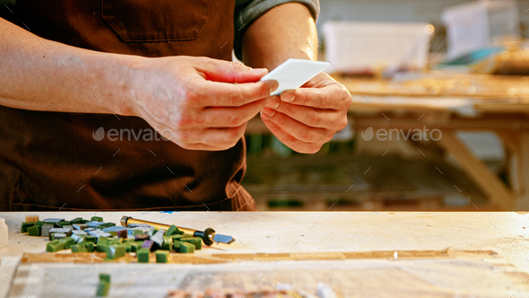 Young man in apron holding a piece of stone close-up - Stock Photo - Images