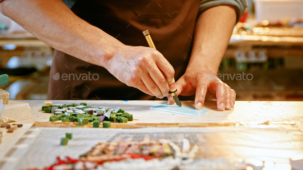 Male hands cutting a piece of glass in creative studio - Stock Photo - Images