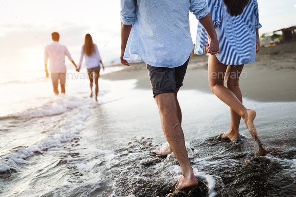 Group of friends having fun and walking on the beach at sunset - Stock Photo - Images