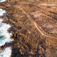Aerial view of the coast and foam of the sea waves, dry terrain and trails, Canary Islands - PhotoDune Item for Sale