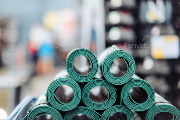 New rolled up yoga and fitness mats on a store shelf. Close view - Stock Photo - Images