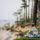 A young woman sits on the shore of a small lake near the forest - PhotoDune Item for Sale