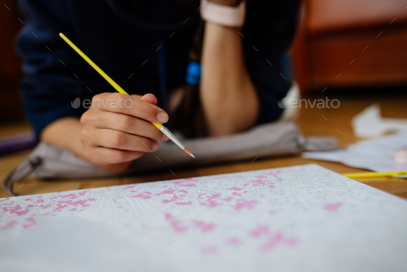 Young woman drawing laying on the floor at home - Stock Photo - Images