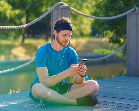 Calm young sportive man in earphones using modern smartphone while resting after exercising in park - Stock Photo - Images