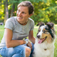 Happy woman spending time with lovely spotted Australian Shepherd dog in green meadow on summer - PhotoDune Item for Sale