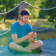 Calm young sportive man in earphones using modern smartphone while resting after exercising in park - PhotoDune Item for Sale