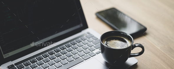 Coffee mug placed on laptop with stock chart on screen, Close up shot. - Stock Photo - Images