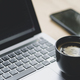 Coffee mug placed on laptop with stock chart on screen, Close up shot. - PhotoDune Item for Sale