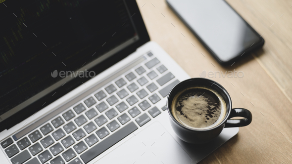Coffee mug placed on laptop with stock chart on screen, Top view shot. - Stock Photo - Images