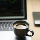 Coffee mug placed on laptop with stock graph on screen, Shot from the front. - PhotoDune Item for Sale