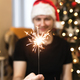 Young man in Santa hat is holding burning sparkler near Christmas tree - PhotoDune Item for Sale