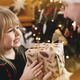 Young father in Santa hat giving Christmas gift to daughter near Christmas tree - PhotoDune Item for Sale