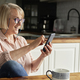 Happy senior woman using smart phone at home - PhotoDune Item for Sale