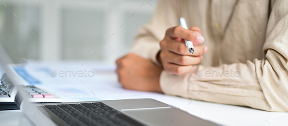 Cropped shot of Businessman holding pen in hand on desk,Business concepts. - Stock Photo - Images