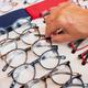 Caucasian hands of woman choosing a pair of eyeglasses full of colors at the outdoor market - PhotoDune Item for Sale