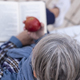 High angle view of a senior woman with gray hair reading a book with an apple in her hands. - PhotoDune Item for Sale