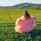 Girl in pink dress walking through green fields at sunset - PhotoDune Item for Sale