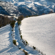 Snowy landscape with a path between fields and mountains in the background - PhotoDune Item for Sale