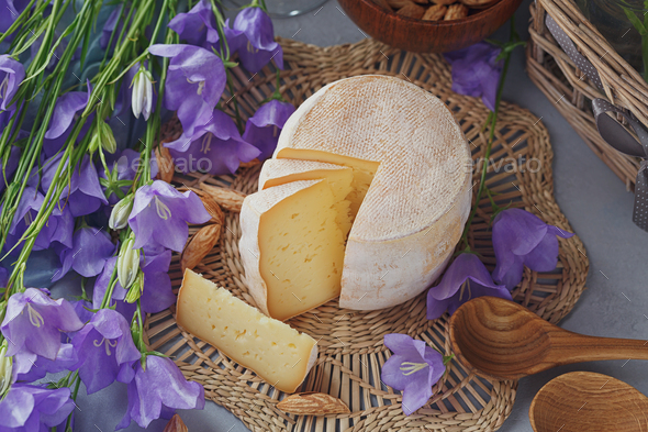 A head of fresh organic cheese served with bread, nuts and summer flowers. - Stock Photo - Images