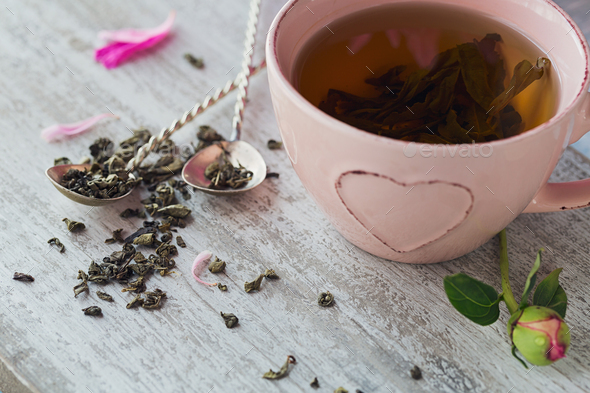 Still life with pink peony flowers and a cup of herbal or green tea - Stock Photo - Images